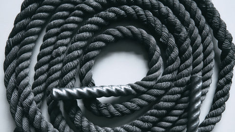Close up of black battle rope on a gray backgound.