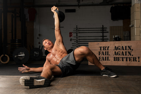 athlete with strong abs is doing the exercise turkish get up with a kettlebell