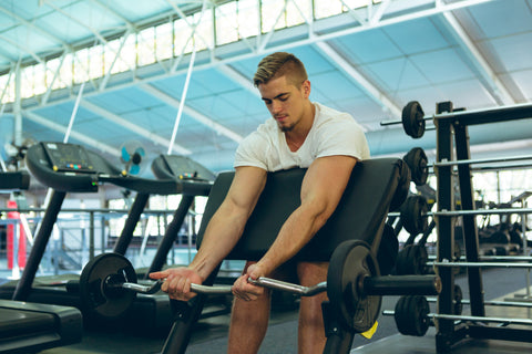 male athletic exercising with barbell on preacher bench in fitness center