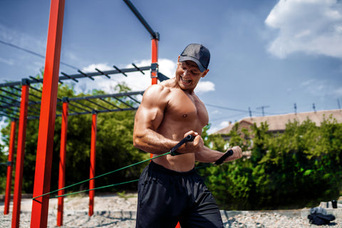 Fitness man training chest with resistance bands at street gym