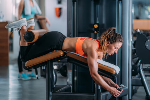 A girl doing a leg curl workout in a gym.