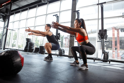 Two people doing bodyweight squats in a gym.