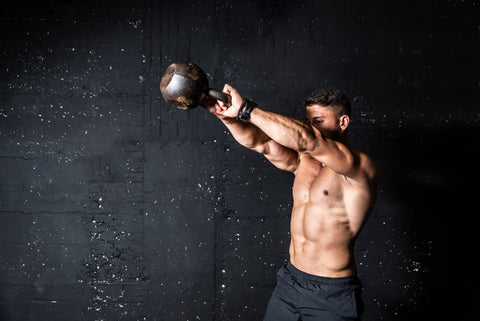 fit muscular man with big muscles holding heavy kettlebell for swing