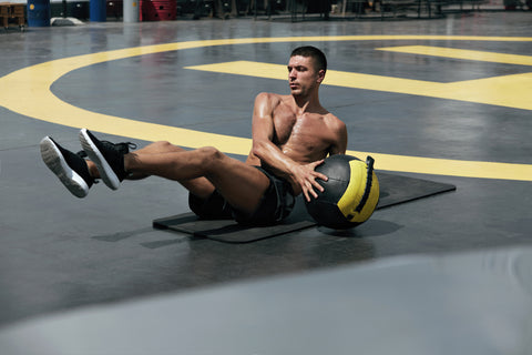 Male athlete exercising, doing russian twist with medicine ball outdoors