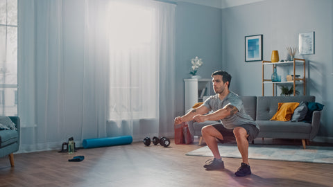 A man doing squats at home.