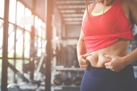 woman holding her belly fat in a gym