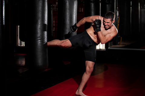 MMA Fighter practicing some kicks with a punching bag at a gym