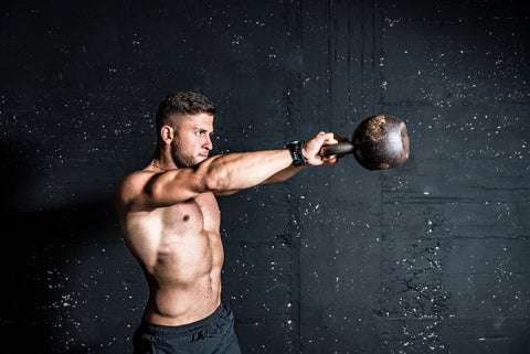 Young strong sweaty focused fit muscular man with big muscles holding heavy kettlebell for swing