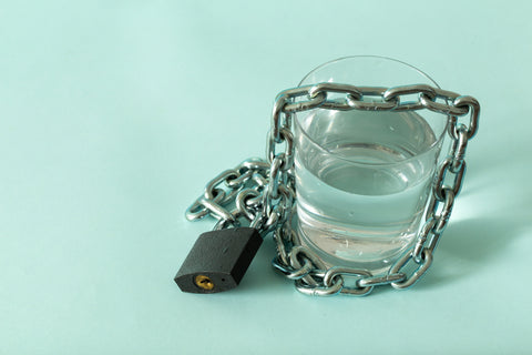 a glass of water wrapped in a chain and closed with a padlock