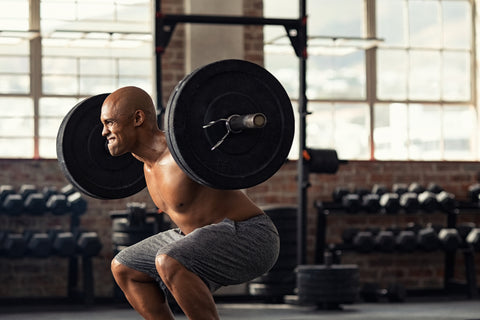 Black shirtless bodybuilder doing squatting with a barbell on shoulder.