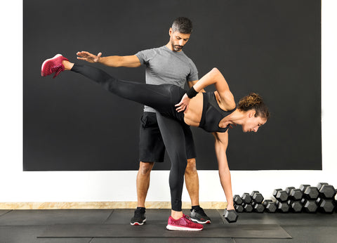 A man and a woman working out in a gym.