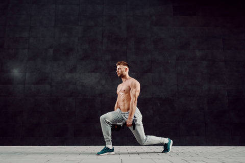 man doing lunges with dumbbells in hands.