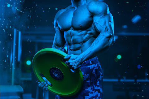 muscular man holding weight plate in gym