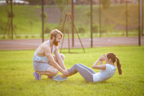 A man helping a girl do crunches in a field.
