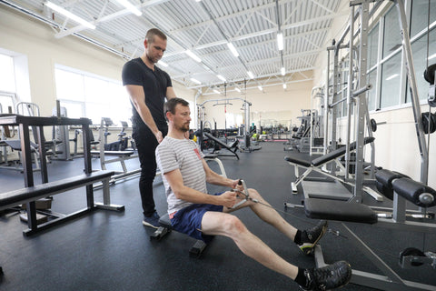 a male beginner training in the gym with a personal trainer