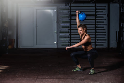 attractive muscular and strong fit girl holding heavy kettlebell for snatch