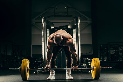 Bodybuilder handsome strong athletic rough man pumping up back muscles deadlift