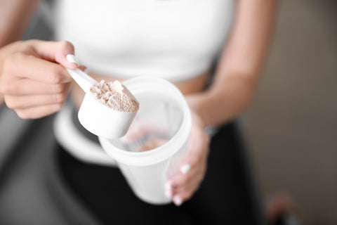 Sporty young woman with protein at home