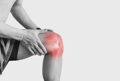 a man touching knee at pain point