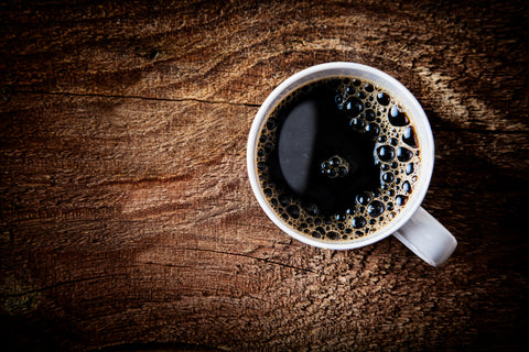 Close up overhead view of a cup of strong frothy espresso coffee on a rough textured wooden surface with dark vignetting and a highlight around the mug