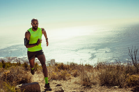 man jogging over rocky trail on mountain