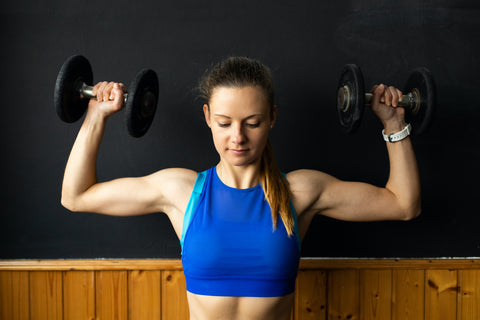 A girl doing a the shoulder press at home.