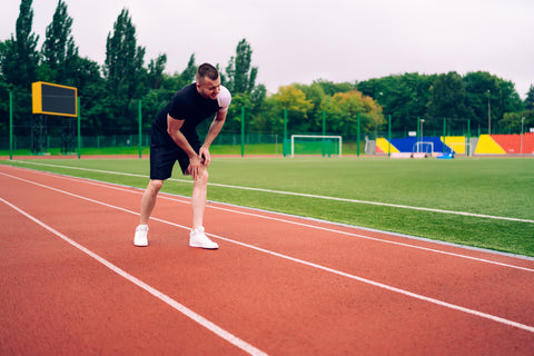 male runner feeling terrible pain in knee after injury