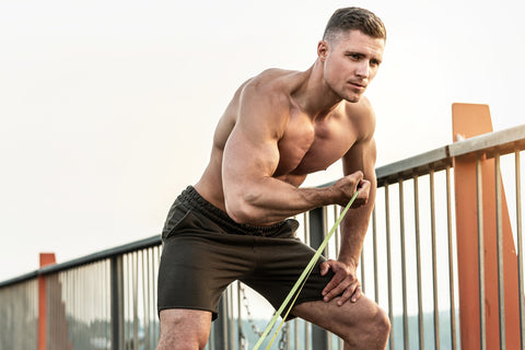 Young and muscular man during workout with a resistance rubber bands on a street
