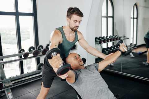 A man and his trainer doing dumbbell flyes.