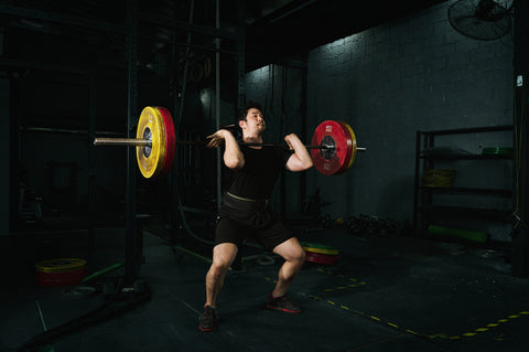 Fit muscular athlete doing clean and jerk exercise in the gym