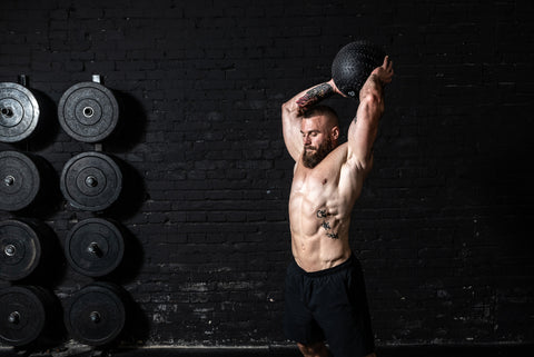 Young sweaty strong muscular fit man with big muscles doing ball throwing on the floor