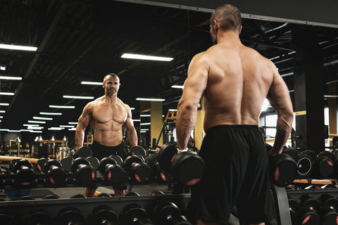 Muscular bodybuilder in a free weights zone in the gym