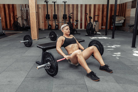 Young athletic strong woman practicing glute bridge exercise with a heavy barbell on her legs