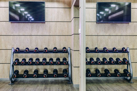 Lots of dumbbells in gym on rack in sport complex