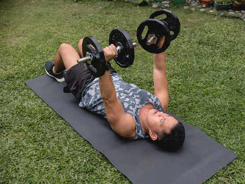 An fit and determined asian male does dumbbell floor presses on a mat at his lawn outdoors.