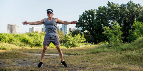 guy doing jumping jacks in a field