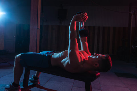 Muscular man does dumbbell pullovers in a gym