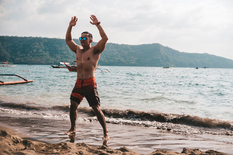 fitness guy doing jumping jacks, star jump or burpees exercise at seaside outdoors