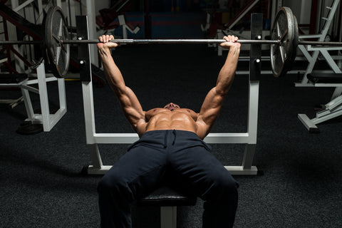 a man doing bench presses at the gym