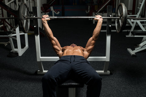A man doing the bench press in a gym.