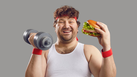 Funny smiling man with dumbbell and delicious burger looking at camera