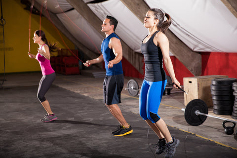 Three people working out with jump ropes in a gym.