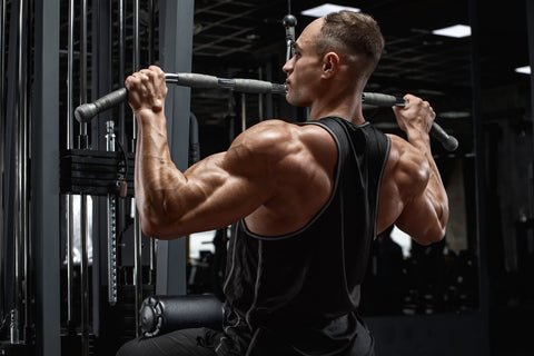 Muscular man workout in gym, doing exercise for back lat pulldown.