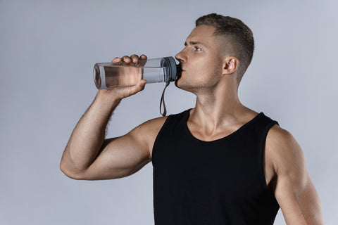 athletic man drinking water against gray background