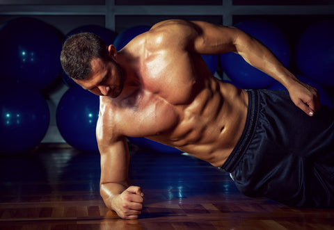 man doing side plank in a gym