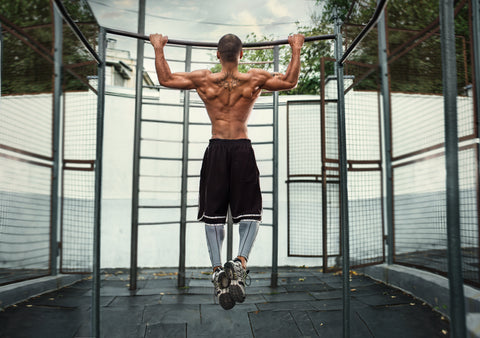 A man doing a pull-up in a gym.