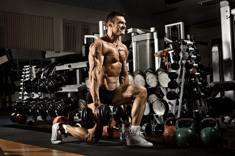 A strong man doing lunges in a gym.