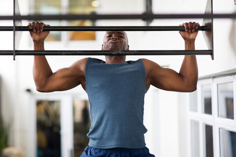 A man doing pull-ups in a gym.