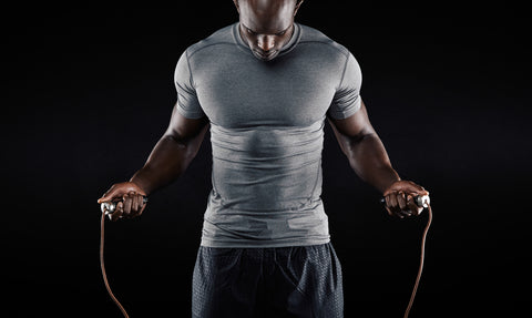 Portrait of muscular young man exercising with jumping rope on black background