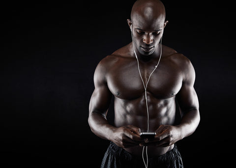 Studio shot of muscular young man listening music on mobile phone against black background